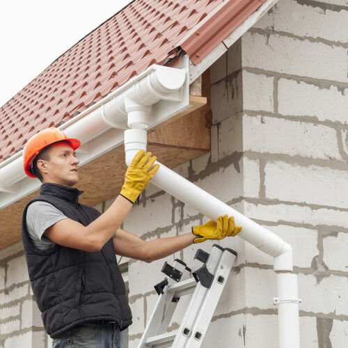 A Roofer Repairs a Downspout.