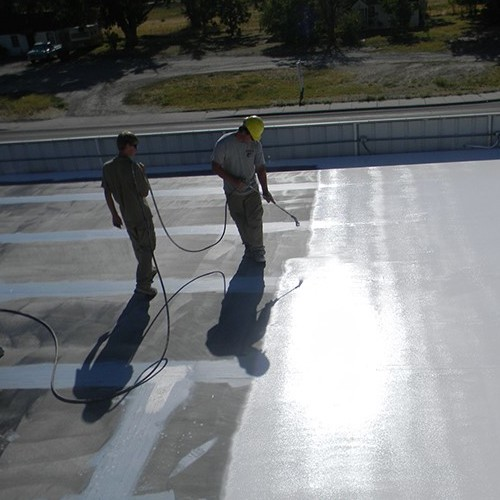 Contractors Apply a Roof Coating.